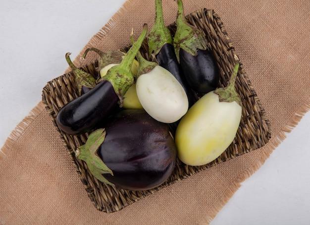Vue de dessus aubergines blanches et noires sur un support sur une serviette beige