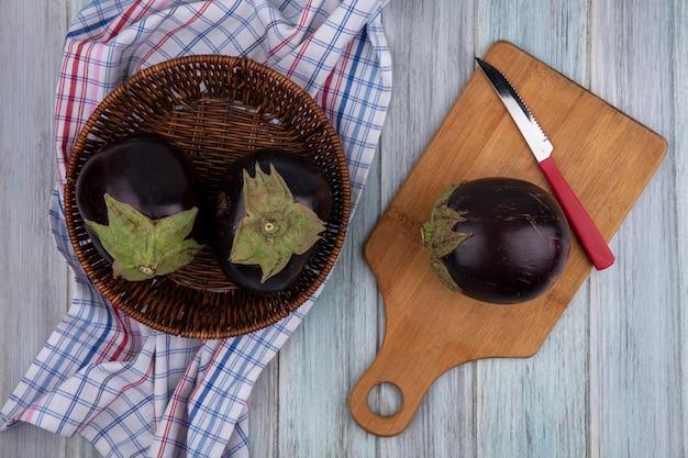 Vue de dessus des aubergines avec couteau sur planche à découper et dans le panier sur tissu à carreaux sur fond de bois