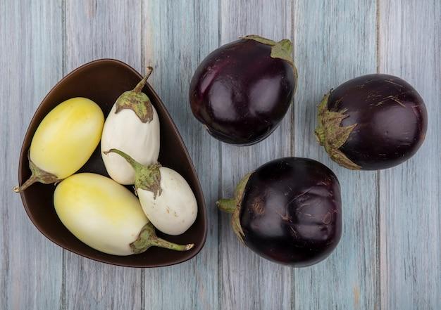 Vue de dessus d'aubergines jaunes et blanches dans un bol et celles de nadia noires sur fond de bois
