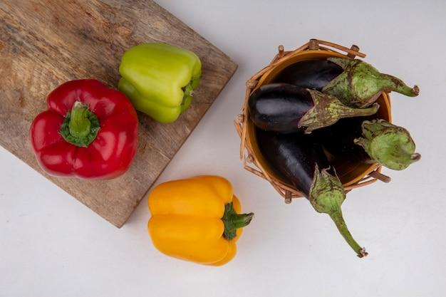 Vue de dessus d'aubergines noires dans un panier avec des poivrons colorés sur une planche à découper