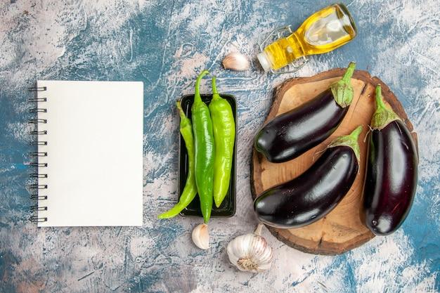 Vue de dessus aubergines sur planche de bois d'arbre piments forts sur plaque noire huile d'ail un cahier sur fond bleu-blanc