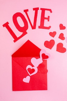 Vue de dessus autocollants coeur rouge amour en lettres majuscules enveloppe sur fond rose