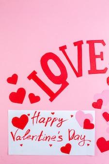 Vue de dessus autocollants coeur rouge joyeux saint valentin écrit sur papier amour en majuscules sur fond rose