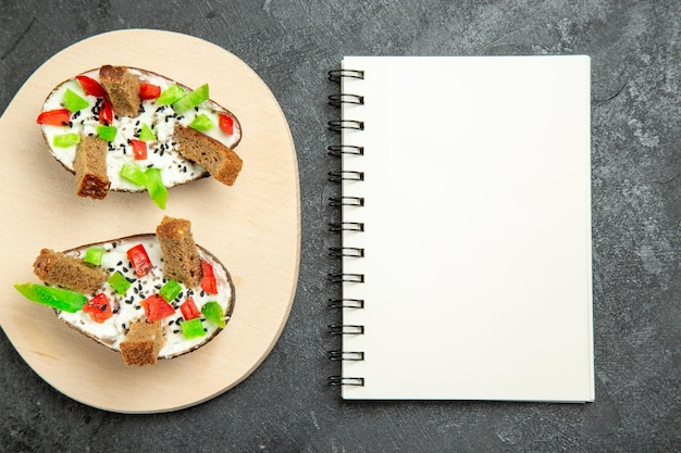 Vue de dessus des avocats crémeux avec des poivrons en tranches et des morceaux de pain avec bloc-notes sur surface grise