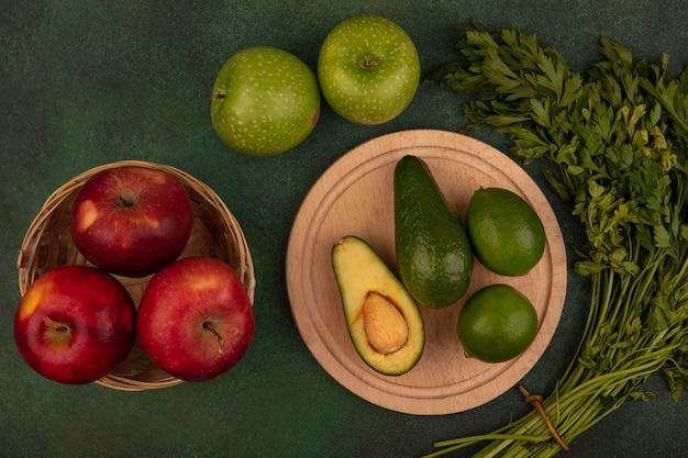 Vue de dessus des avocats à peau verte sur une planche de cuisine en bois avec des limes aux pommes rouges sur un seau avec des pommes vertes et du persil isolé sur fond vert