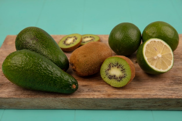 Vue de dessus des avocats sains avec des limes et des kiwis sur une planche de cuisine en bois sur un mur bleu
