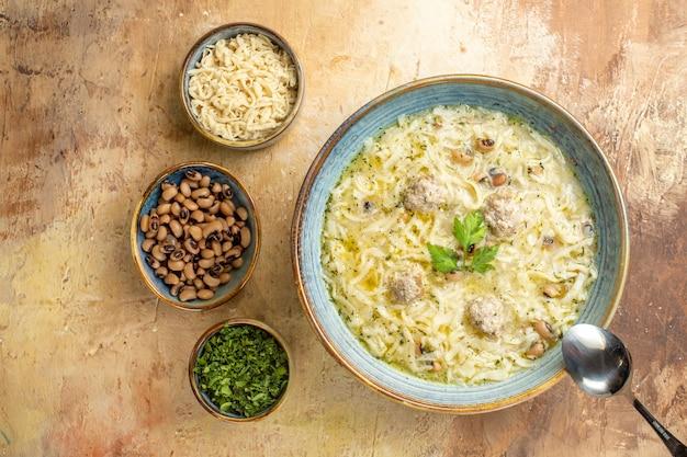 Vue de dessus azerbaijani erishte dans un bol une cuillère différentes choses dans des bols sur fond beige