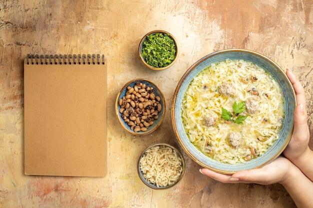 Vue de dessus azerbaijani erishte dans un bol en femme mains différentes choses dans des bols un cahier sur fond beige