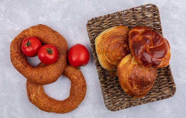 Vue de dessus des bagels au sésame turc avec des tomates fraîches et un seau de petits pains sur fond blanc