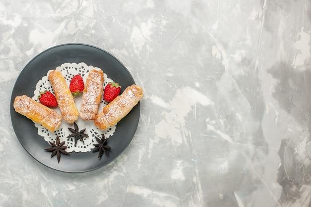 Vue de dessus des bagels en poudre de sucre pâte délicieuse avec des fraises sur une surface blanche