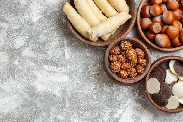 Vue de dessus des bagels sucrés avec des biscuits et des noix sur une surface blanche