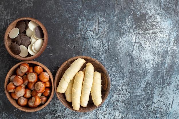 Vue de dessus des bagels sucrés avec des noix et des biscuits sur une surface sombre