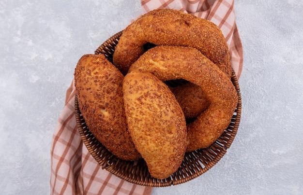 Vue de dessus de bagels turcs frais sur un seau sur un chiffon à carreaux sur fond blanc