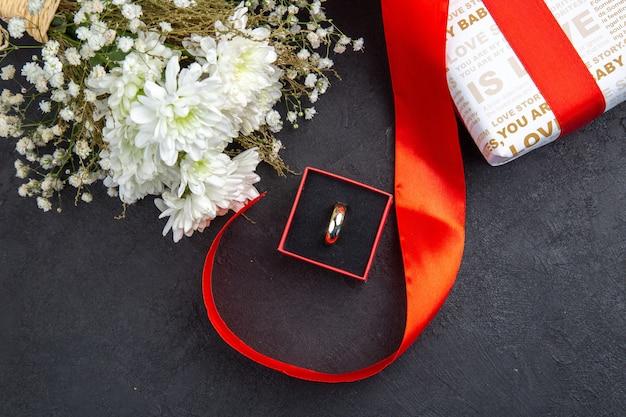 Vue de dessus bague cadeau saint valentin en boîte fleurs sur fond sombre
