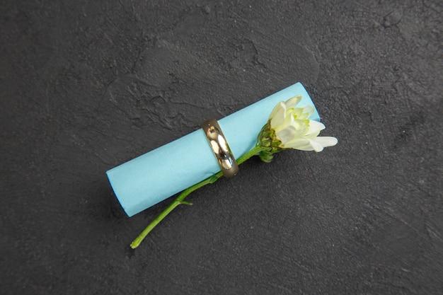 Vue de dessus bague de fiançailles défilement papier de souhaits et marguerite sur fond sombre