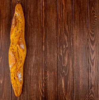 Vue de dessus de la baguette sur le côté gauche et fond en bois avec espace copie