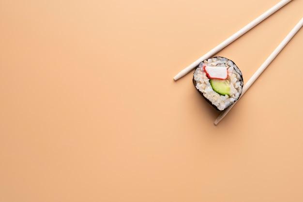 Vue de dessus des baguettes tenant des sushis