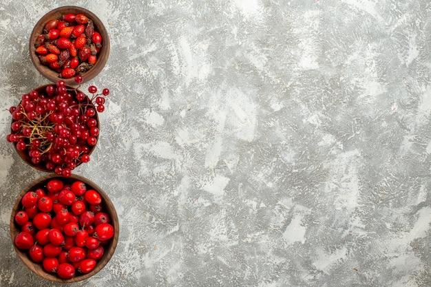Vue de dessus baies rouges fruits moelleux sur fond blanc