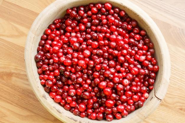 Vue de dessus des baies rouges vives dans un bol en bois. baies mûres sur un fond en bois