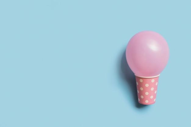 Vue de dessus ballon de couleur pastel à l'intérieur du gobelet en papier