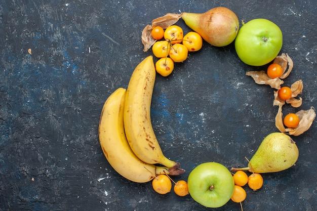 Vue de dessus bananes jaunes paire de baies avec des pommes vertes fraîches poires cerises douces sur le bureau bleu foncé baies de fruits frais santé