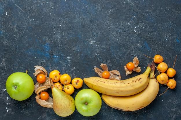 Vue de dessus bananes jaunes paire de baies avec des pommes vertes fraîches poires cerises douces sur le bureau bleu foncé fruits baies santé vitamine