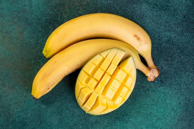 Vue de dessus des bananes avec des mangues hachées sur une table verte