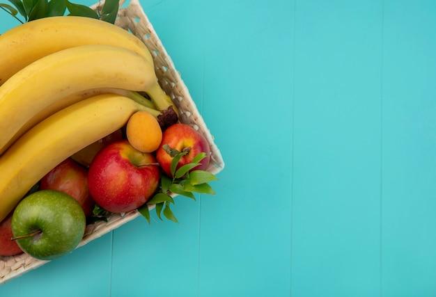 Vue de dessus des bananes avec des pommes colorées et des pêches dans un panier avec des branches sur une surface turquoise