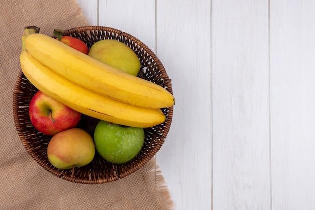 Vue de dessus des bananes avec des pommes dans un panier sur une surface blanche