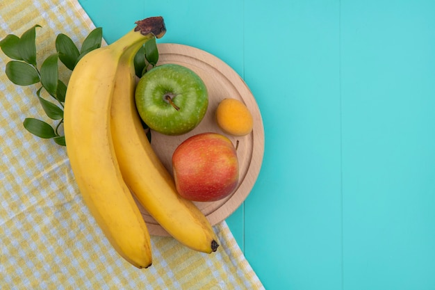 Vue de dessus des bananes avec des pommes sur un support sur une serviette à carreaux jaune sur une surface bleue