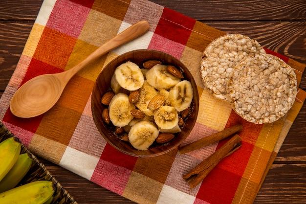 Vue de dessus des bananes en tranches aux amandes dans un bol et des cuillères en bois avec des craquelins de riz et des bâtons de cannelle sur rustique