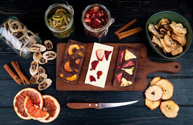 Vue de dessus des barres de chocolat noir et blanc sur une planche à découper en bois avec divers fruits en tranches séchées sur fond noir
