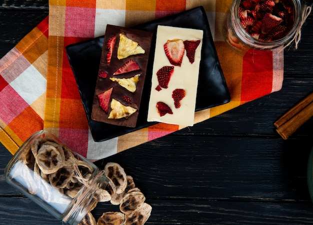 Vue de dessus des barres de chocolat noir et blanc sur un plateau noir avec divers fruits en tranches séchées dans des bocaux en verre sur fond noir avec copie espace