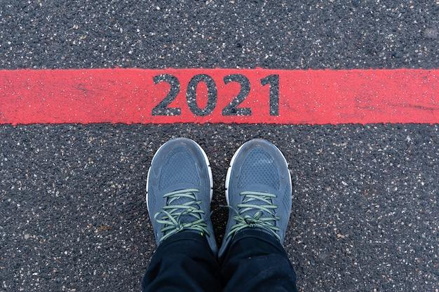 Vue de dessus des baskets masculines sur la route goudronnée avec texte 2021 sur la ligne rouge, concept de célébration du nouvel an