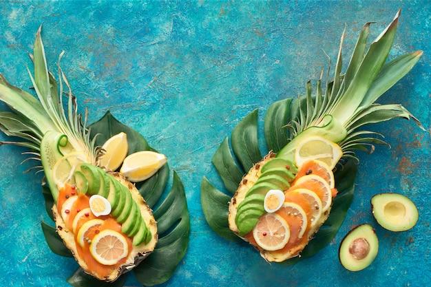 Vue de dessus sur des bateaux à ananas avec du saumon fumé et des tranches d'avocat avec des œufs de citron et de caille
