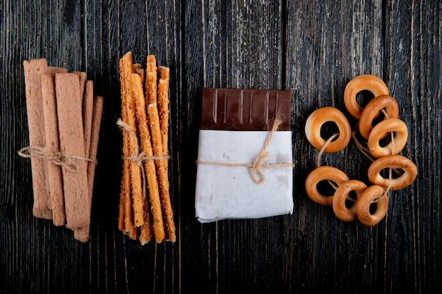 Vue de dessus des bâtons de maïs avec des baguettes de pain au chocolat et des bagels secs sur un fond en bois noir
