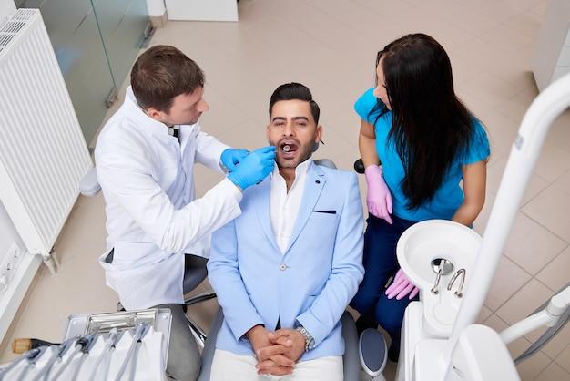 Vue de dessus d'un beau jeune homme ayant un examen oral au bureau du dentiste