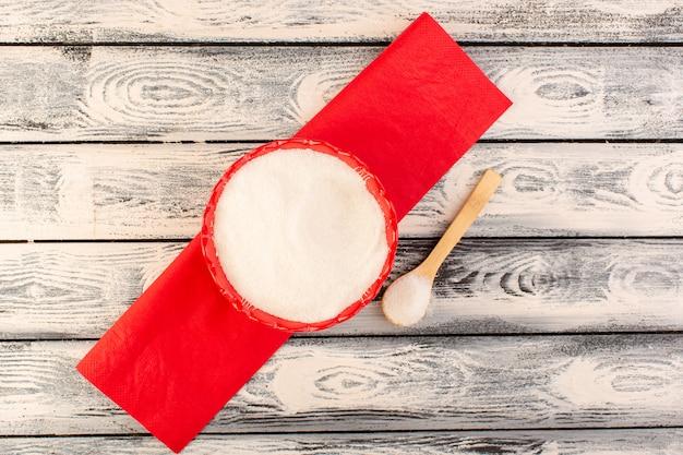 Une vue de dessus beaucoup de sel à l'intérieur de la plaque ronde rouge avec une cuillère en bois sur le bureau gris