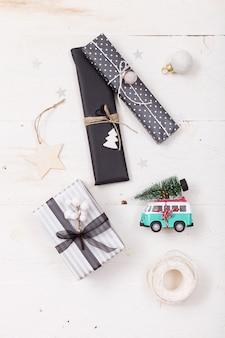 Vue de dessus sur de beaux cadeaux de noël emballés dans du papier noir et rayé et une mini-fourgonnette rétro