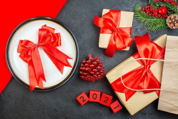 Vue de dessus de beaux cadeaux et ruban en forme d'arc sur une assiette de branches de sapin conifère cône numéros sur une table sombre