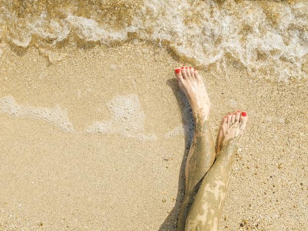 Vue de dessus de beaux pieds féminins avec pédicure rouge vif sur le sable de la plage les chevilles des pieds sont enduites de rajeunissement de la peau de boue médicinale tout en se relaxant dans l'espace de copie du spa de la mer