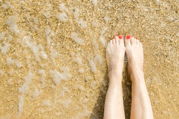Vue de dessus de beaux pieds féminins avec pédicure rouge vif sur le sable de la plage, la vague de la mer lave les pieds des femmes détente et plaisir pendant votre espace de copie de vacances à la mer