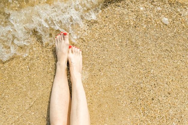 Vue de dessus de beaux pieds féminins avec pédicure rouge vif sur le sable de la plage.