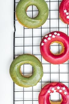 Vue de dessus des beignets au four avec glaçage rose et vert vif, étoile saupoudrée sur une grille de refroidissement