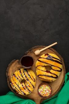 Vue de dessus beignets délicieux délicieux sur le bureau brun et le sol sombre