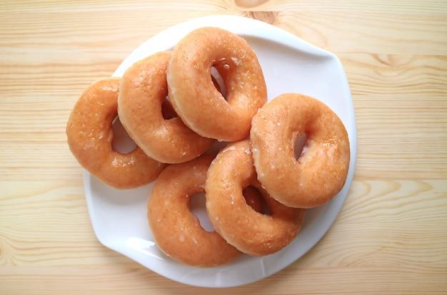 Vue de dessus de beignets glacés au sucre servis sur une plaque blanche sur une table en bois