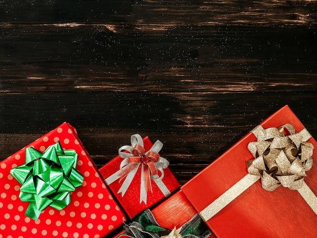 Vue de dessus de la belle boîte-cadeau rouge avec des décorations d'arc vert et or brillant sur planche de bois foncé