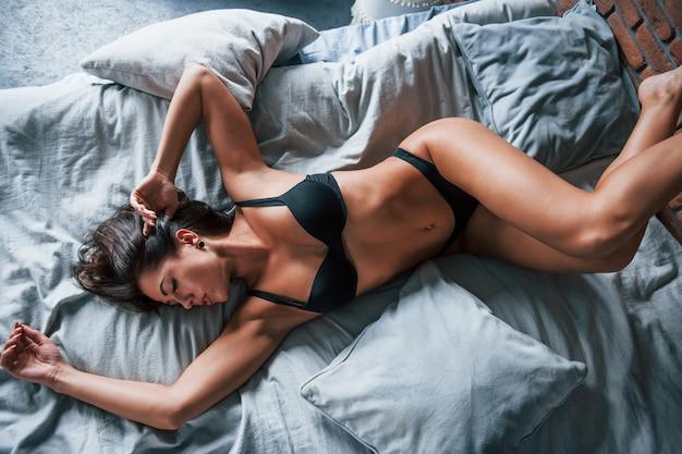 Vue de dessus de la belle femme brune sexy qui est sur le lit le matin.