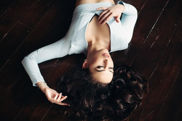 Vue de dessus de belle femme en robe bleue se trouvant sur un plancher en bois foncé.