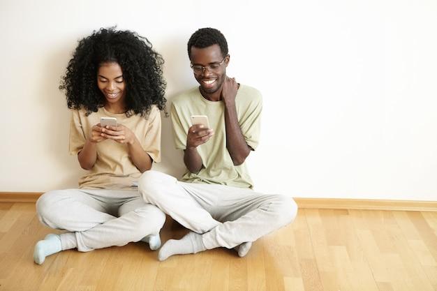 Vue de dessus de la belle jeune femme avec une coiffure afro vérifiant le fil d'actualité via les réseaux sociaux